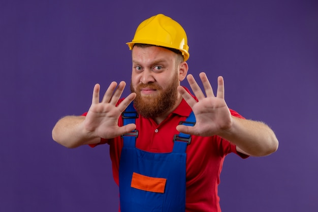 Young bearded builder man in construction uniform and safety helmet making rejection defense gesture with open hands, with disgusted expression over purple background Free Photo