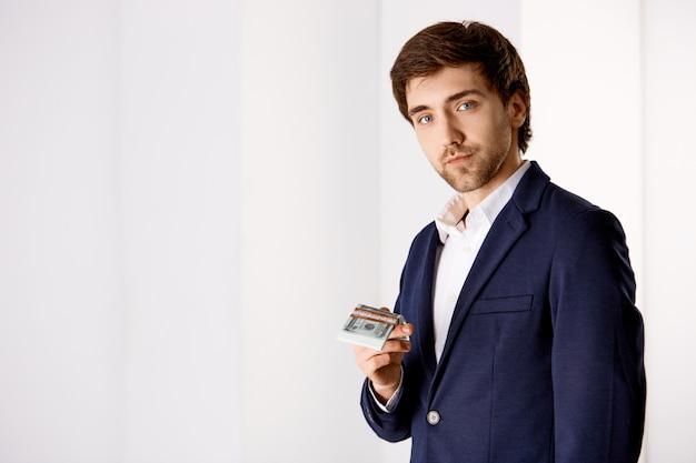 お金を保持しているスーツを着た若いひげを生やしたビジネスマン、良い給与、安定した収入を示唆する笑顔、会社を探す従業員 無料写真