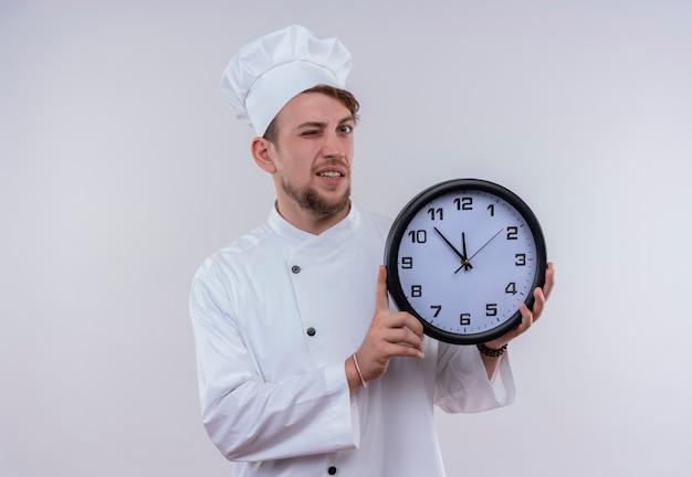 Un giovane chef barbuto uomo che indossa bianco uniforme da cucina e cappello che mostra orologio da parete e strizza l'occhio mentre guarda su un muro bianco Foto Gratuite