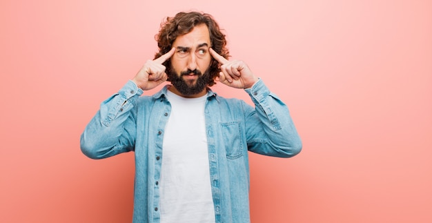 Young bearded crazy man feeling confused or doubting, concentrating on an idea, thinking hard, looking to copyspace on side against flat color Premium Photo