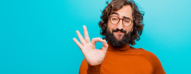 Young bearded crazy man feeling happy, relaxed and satisfied, showing approval with okay gesture, smiling against flat color wall Premium Photo