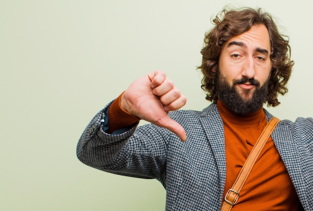 Young bearded crazy man looking sad, disappointed or angry, showing thumbs down in disagreement, feeling frustrated Premium Photo