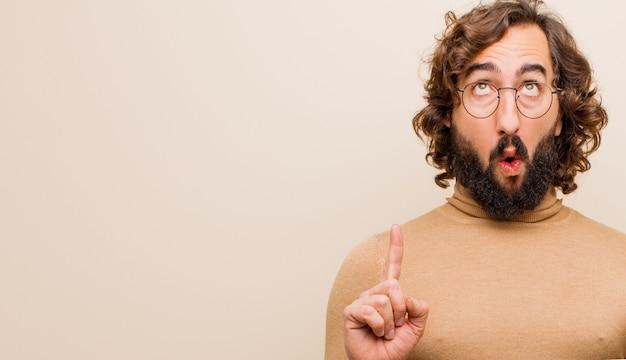 若いひげを生やした狂気の男見てショックを受け、驚いて、口を開けて、フラットカラーの壁に対してスペースをコピーするために両手で上向き Premium写真