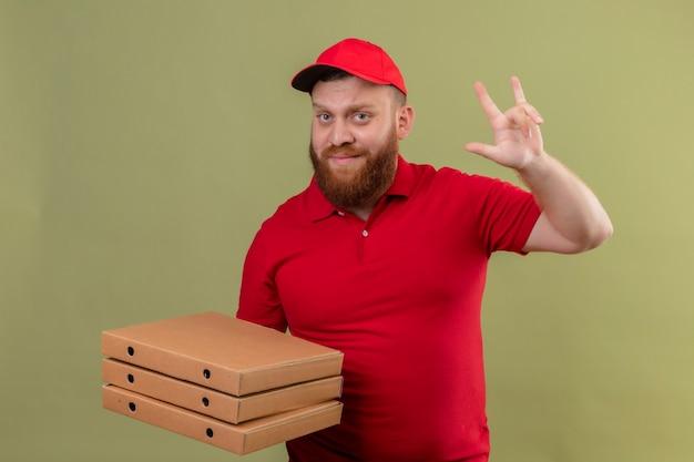 赤い制服と帽子の若いひげを生やした配達人は、ロックのシンボルをやって自信を持って見えるピザボックスのスタックを保持しています 無料写真