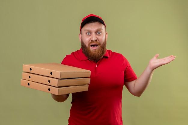 赤い制服と帽子をかぶった若いひげを生やした配達人は、心配して腕を上げて混乱しているように見えるピザの箱のスタックを保持しています 無料写真