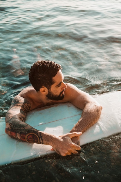 Young bearded guy lying on surf board in water Free Photo