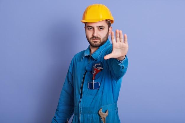 Il giovane operaio bello barbuto con il casco giallo e l'uniforme che fanno il gesto di arresto con la sua mano che nega la situazione Foto Gratuite