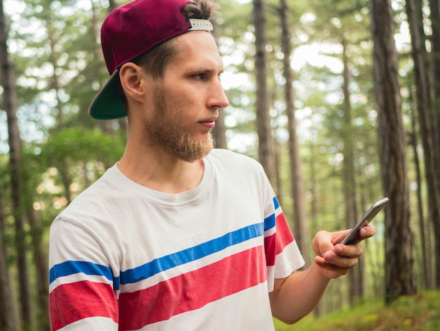 Young bearded hipster blogger make live stream in social network  walking in forest Premium Photo
