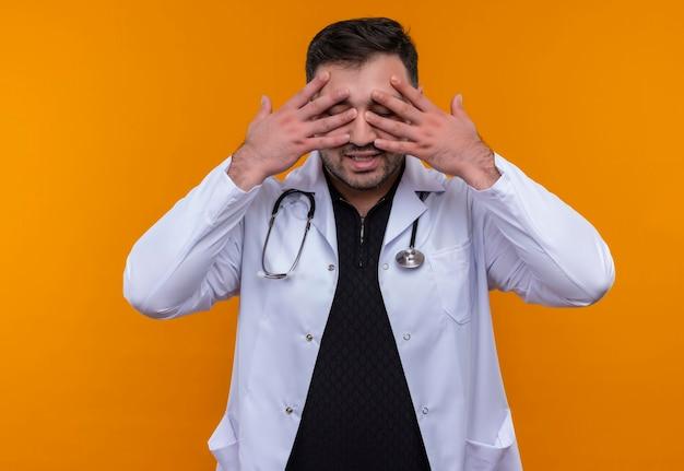 手のひらで目を閉じる聴診器で白衣を着た若いひげを生やした男性医師 無料写真