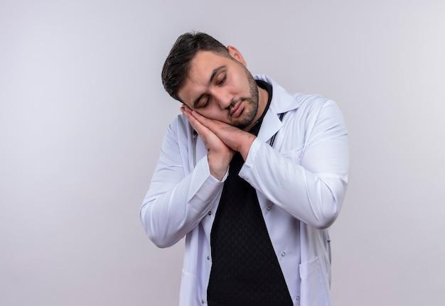 手のひらに頭を傾けて聴診器で白いコートを着ている若いひげを生やした男性医師 無料写真