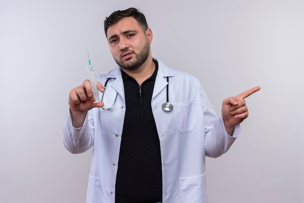 Молодой бородатый мужчина-врач в белом халате со стетоскопом держит шприц в замешательстве, указывая пальцем в сторону Бесплатные Фотографии