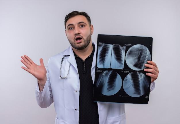 Молодой бородатый мужчина-врач в белом халате со стетоскопом и рентгеновским снимком легких выглядит удивленным и шокированным Бесплатные Фотографии
