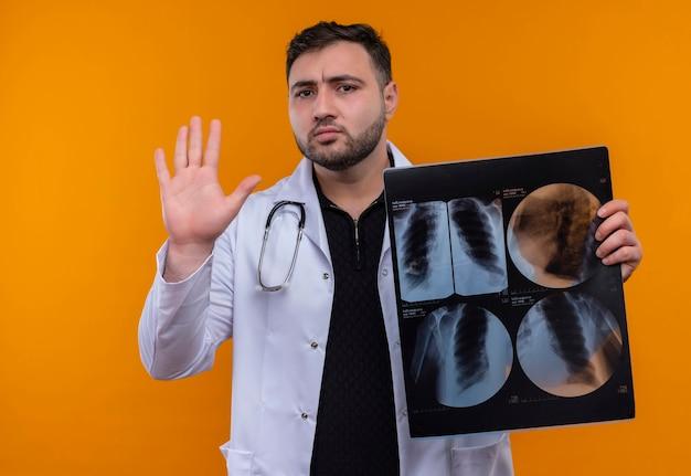 Молодой бородатый мужчина-врач в белом халате со стетоскопом держит рентген легких, делая знак остановки рукой Бесплатные Фотографии