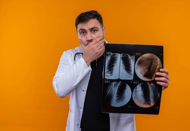 Молодой бородатый мужчина-врач в белом халате со стетоскопом держит в шоке рентгеновский снимок легких, прикрывая рот рукой Бесплатные Фотографии