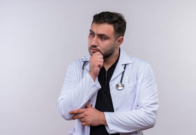 Молодой бородатый мужчина-врач в белом халате со стетоскопом смотрит в сторону, положив руку на подбородок с задумчивым выражением лица Бесплатные Фотографии