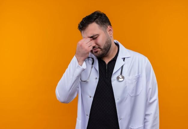 聴診器で白衣を着た若いひげを生やした男性医師は、目を閉じて疲れて退屈な鼻に触れているように見えます 無料写真