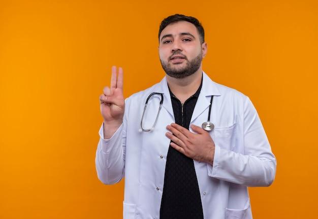 自信を持って見える誓いを立てて聴診器で白衣を着た若いひげを生やした男性医師 無料写真