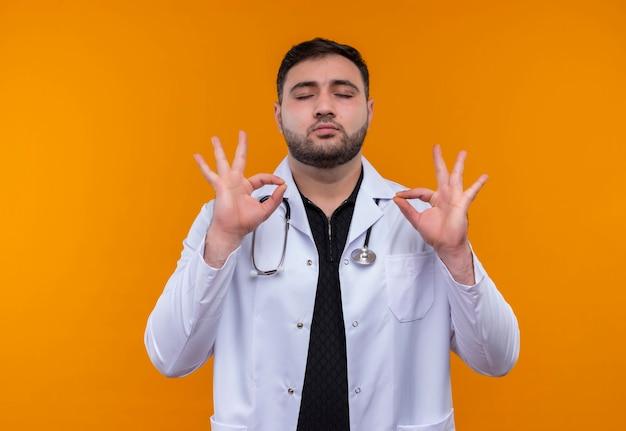 目を閉じてリラックスした聴診器で白衣を着て、指で瞑想の兆候を作る若いひげを生やした男性医師 無料写真