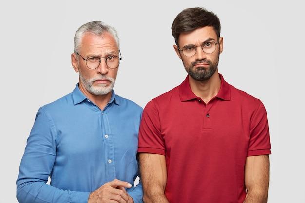 Молодой бородатый самец недоуменно приподнимает бровь, одет в красную футболку, стоит рядом со своим зрелым отцом, проводит выходные в семейном кругу, изолированном над белой стеной. концепция отношений Бесплатные Фотографии