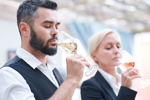 Young bearded male sommelier and his female colleague smelling new sorts of wine in wineglasses before tasting it Premium Photo