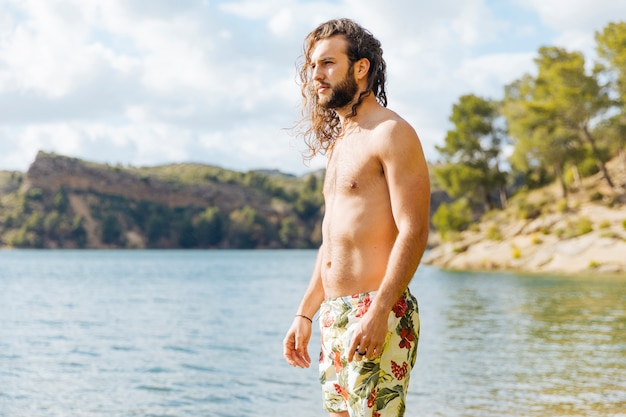 Young bearded male standing near lake Free Photo