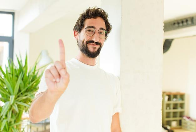 젊은 남자 집에서 수염. 자랑스러운 표정 프리미엄 사진