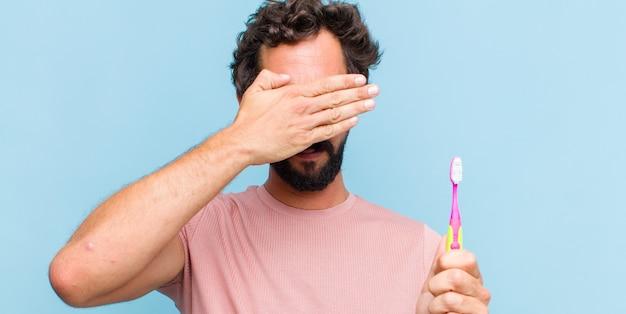한 손으로 두렵거나 불안하거나 궁금해하거나 맹목적으로 놀라움을 기다리는 젊은 수염 난 남자 프리미엄 사진