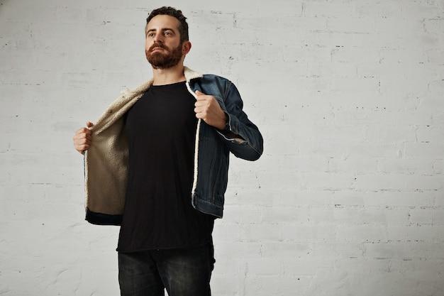 Giovane uomo barbuto in giacca di jeans con fodera di shearling mostra il petto che indossa camicia a maniche lunghe henley nero senza etichetta, isolato sul muro di mattoni bianchi nel club Foto Gratuite