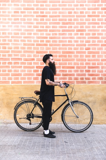 Young bearded man drinking coffee while standing on his bicycle outdoors Free Photo