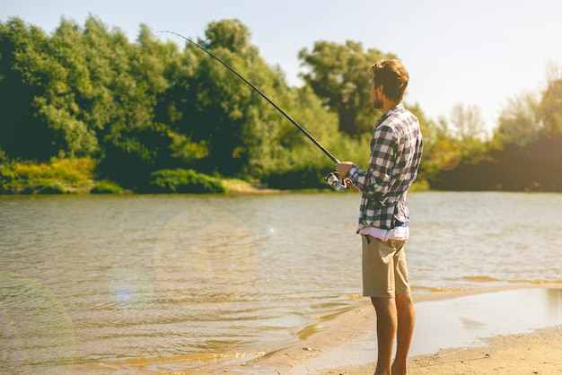 Young bearded man fishing standing on the sandy river bank with fish-rod during summer. Premium Photo