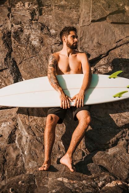 Youngbeardedman holding surf board near stones Free Photo