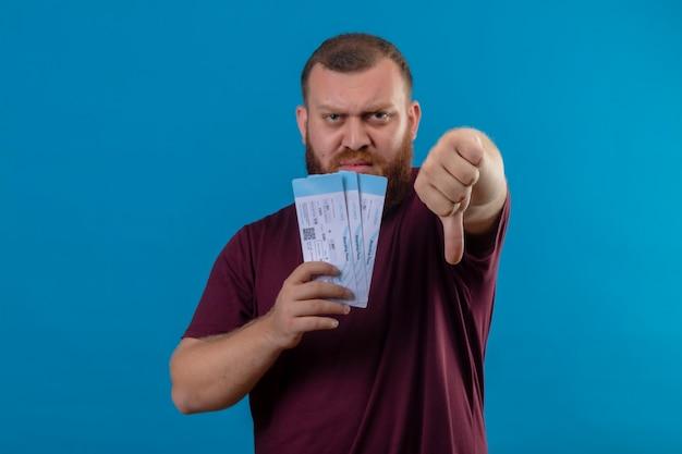 親指を下に見せて不機嫌そうに見える航空券を保持している茶色のtシャツの若いひげを生やした男 無料写真