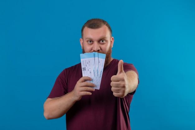 親指を立てて航空券を保持している茶色のtシャツの若いひげを生やした男 無料写真