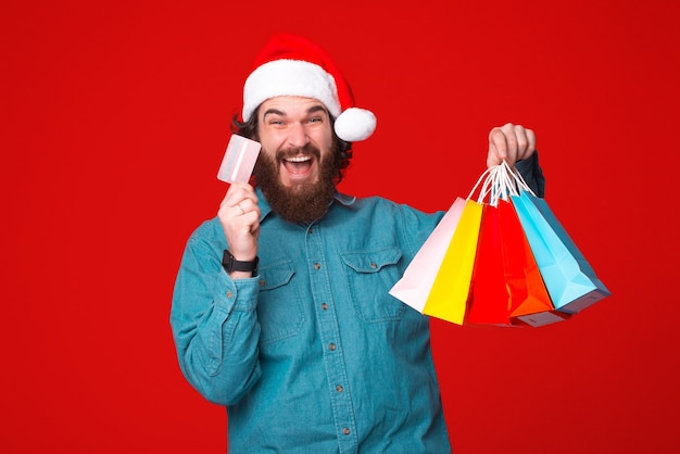 Young bearded man is excited about paying with credit card for his purchases. Premium Photo