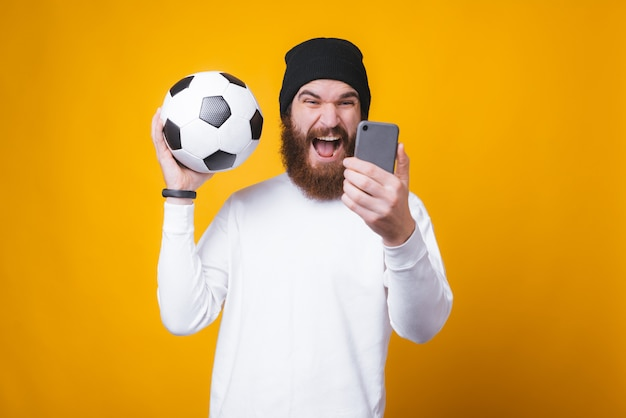 Young bearded man is taking a selfie and holding a soccer ball near yellow wall. Premium Photo