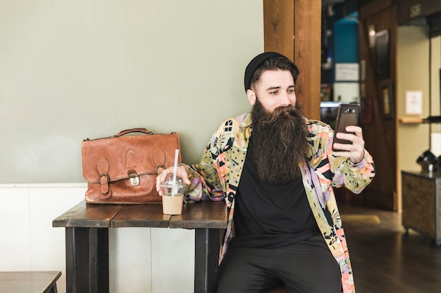 Young bearded man sitting in cafe taking selfie on mobile phone Free Photo