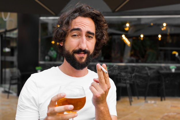 Young bearded man smoking and drinking a beer Premium Photo