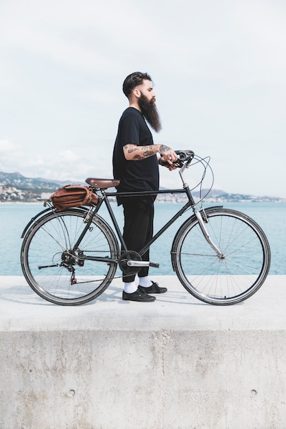 Young bearded man standing with bicycle on breakwater Free Photo