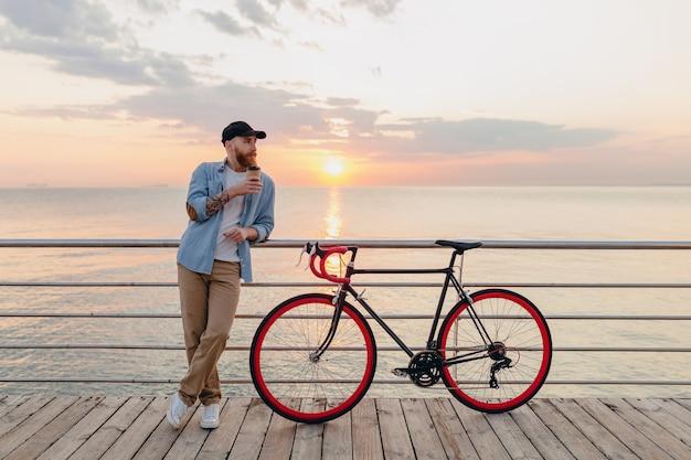 Giovane uomo barbuto che viaggia in bicicletta al tramonto sul mare Foto Gratuite
