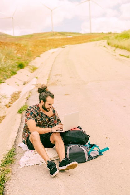Young bearded man using laptop sitting on road Free Photo