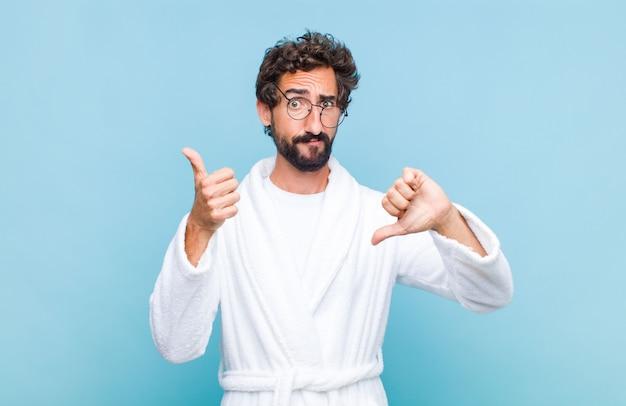 バスローブを着た若いひげを生やした男は、混乱し、無知で、確信が持てず、さまざまなオプションや選択肢で良い点と悪い点に重みを付けています Premium写真