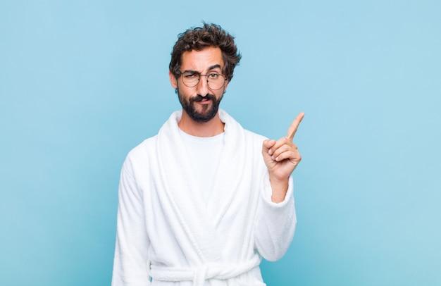 素晴らしいアイデアを実現した後、天才が誇らしげに指を空中に持ち上げているようなバスローブを着た若いひげを生やした男は、ユーレカと言った Premium写真