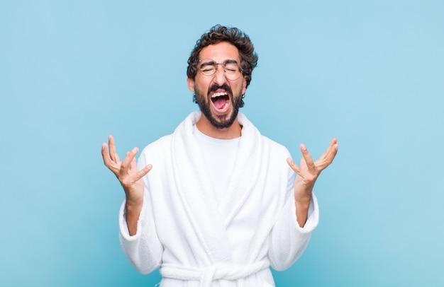 バスローブを着た若いあごひげを生やした男が猛烈に叫び、ストレスを感じ、空中に手を上げてイライラし、なぜ私が Premium写真