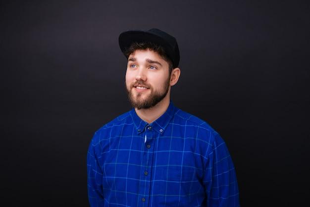 何かを夢見て将来を見つめる青い目と青いシャツを着た若いひげを生やした男。 Premium写真