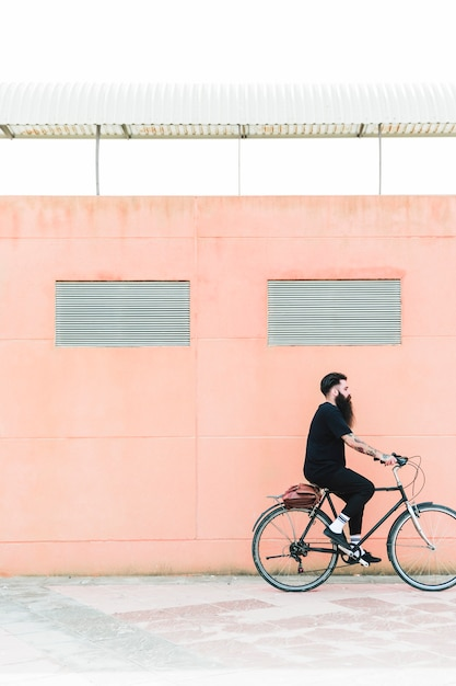 Young bearded man with shoulder bag riding a bike on the city street Free Photo