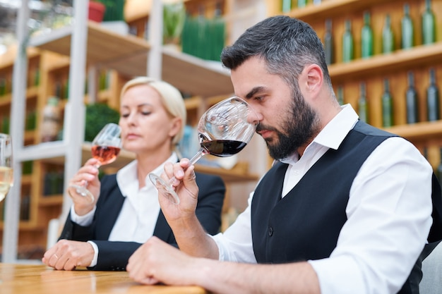 Young bearded sommelier in formalwear smelling new sort of red wine in wineglass while examining its quality Premium Photo