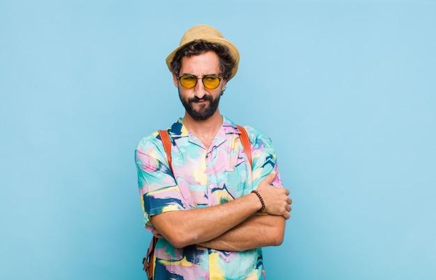 Молодой бородатый турист, грустный, расстроенный или сердитый, смотрит в сторону с отрицательным отношением, хмурясь в знак несогласия Premium Фотографии