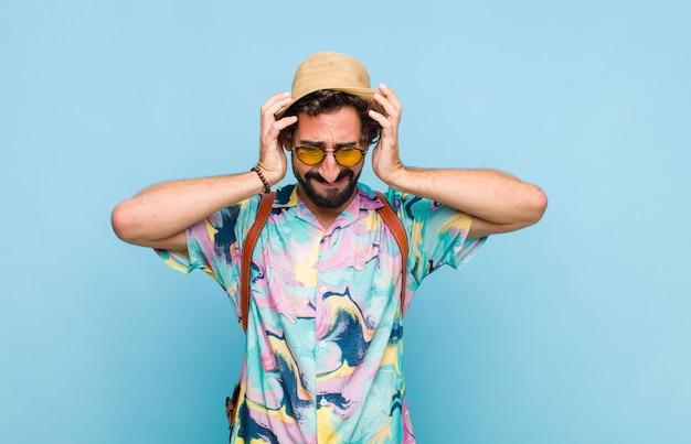 Молодой бородатый турист, чувствуя стресс и разочарование, поднимает руки к голове, чувствует себя усталым, несчастным и страдает мигренью Premium Фотографии