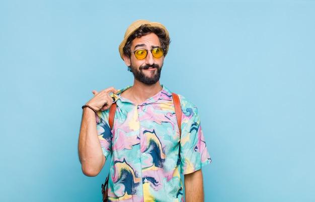 Молодой бородатый турист, чувствуя стресс, тревогу, усталость и разочарование, дергает за шею рубашки и выглядит разочарованным из-за проблемы Premium Фотографии