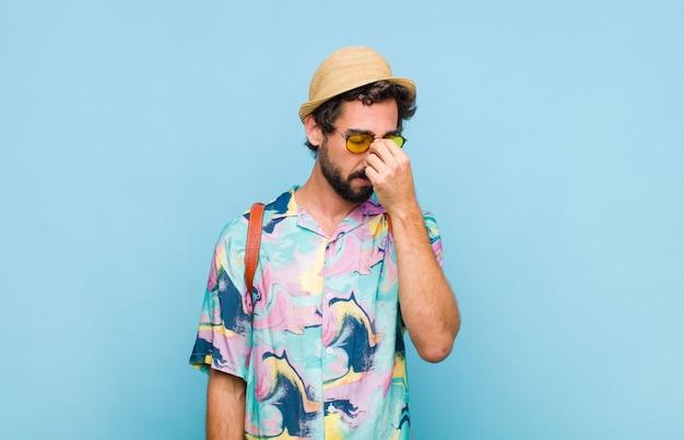 Молодой бородатый турист, чувствующий себя напряженным, несчастным и разочарованным, трогает лоб и страдает от сильной мигрени Premium Фотографии